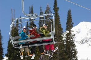 people smiling at camera from ski lift