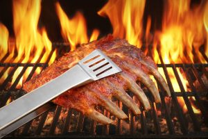 ribs being held by tongs on flaming grill