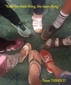 """various feet making a circle with """"keep the main thing, the main thing"""" text overlay"""