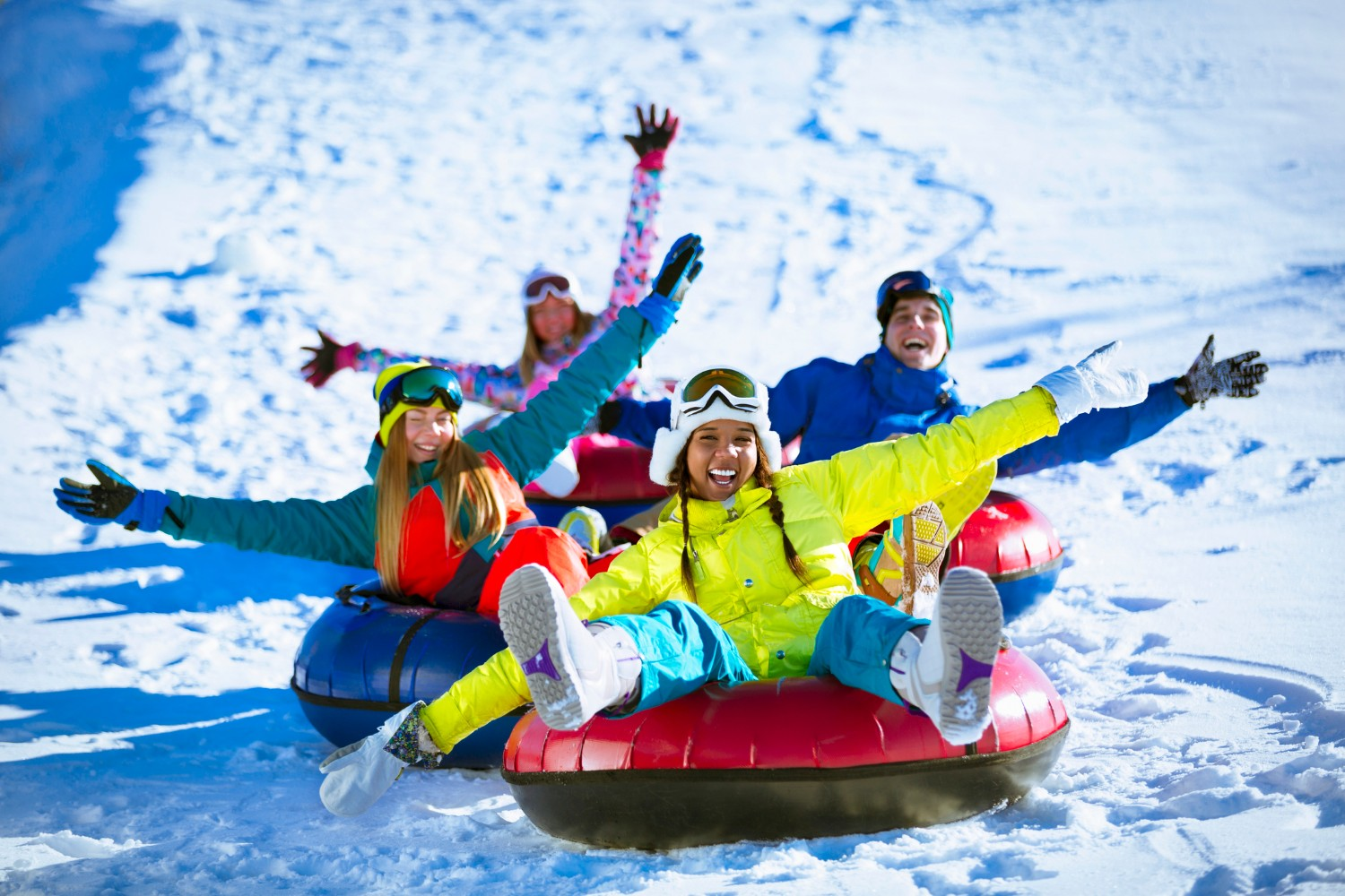 Happy people snow tubing down a hill