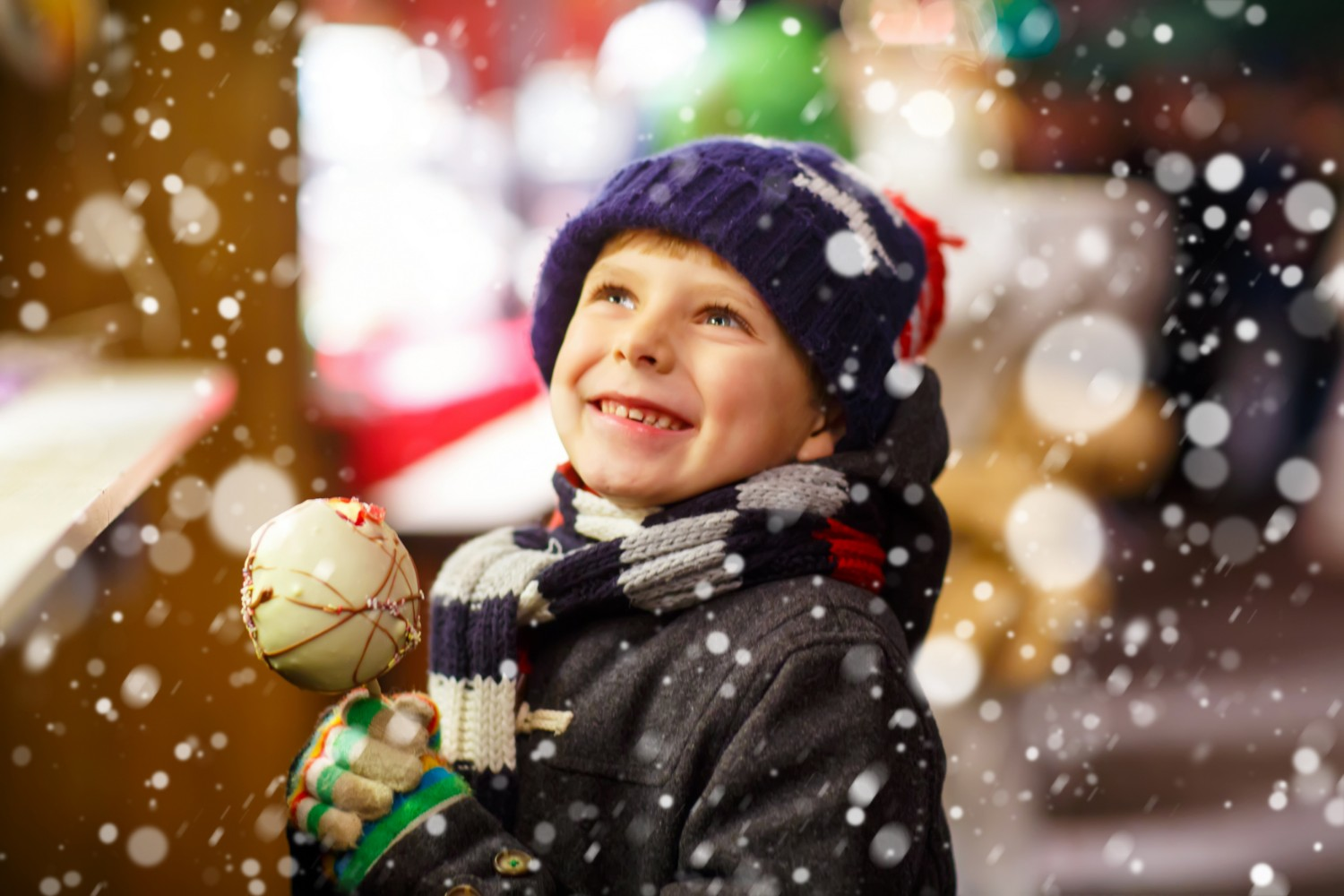 Child standing in the snow holding a caramel apple