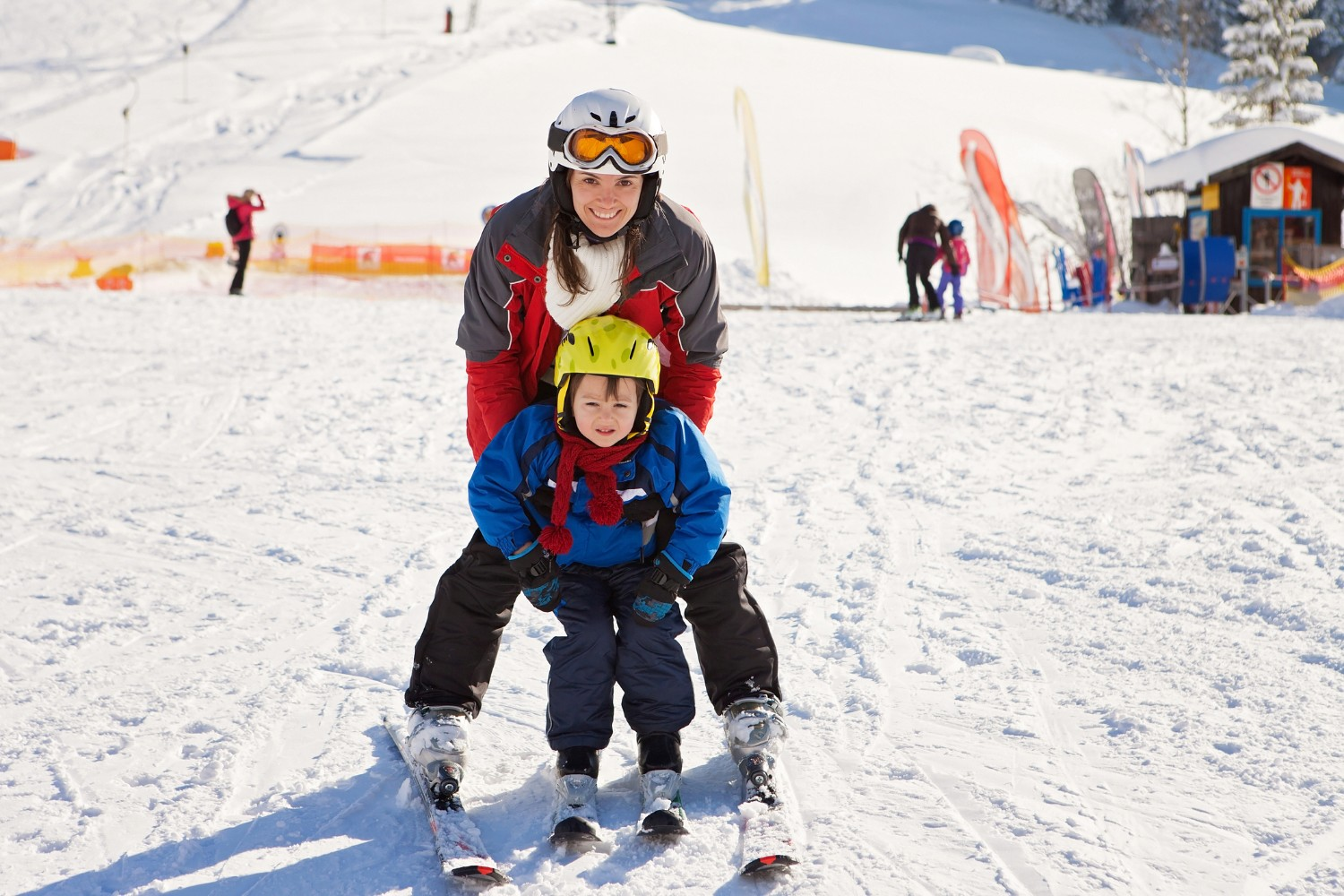 mom and young son skiing together