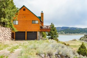 The exterior of Panguitch Lake Cabin rental with Panguitch Lake in the background