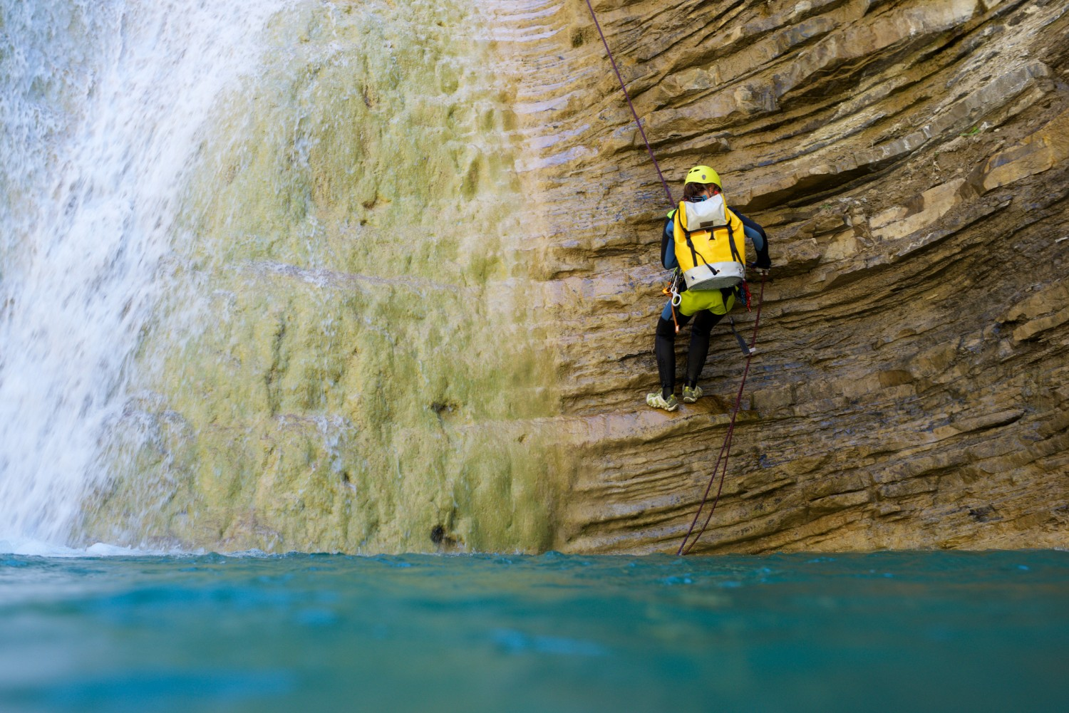 Person scaling a canyon wall above water
